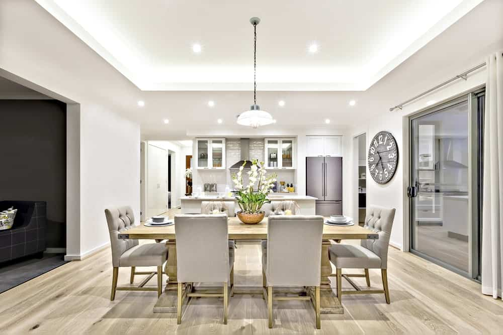 Bright dining room with modern style featuring beige tufted chairs paired with a wooden dining table, beige walls, hardwood flooring and tray ceiling fitted with a dome pendant light and recessed lighting.