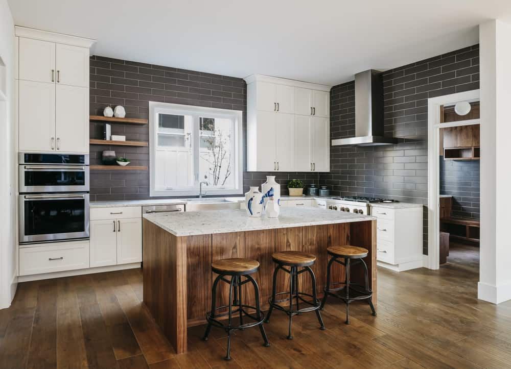 Modern kitchen with wide plank flooring, black brick walls, white cabinetry, marble top island and matching bar stools.