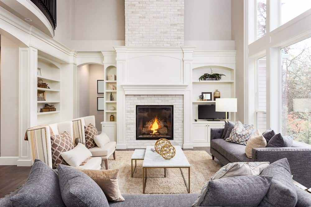 Modern living room with white walls, large windows, hardwood flooring topped by a beige rug, gray fabric sofas, white wingback chairs, modular coffee table and a modern fireplace with brick surround.