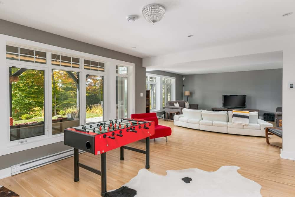 Modern man cave with a cozy living space, game area, hardwood flooring and glazed windows overlooking the serene yard.