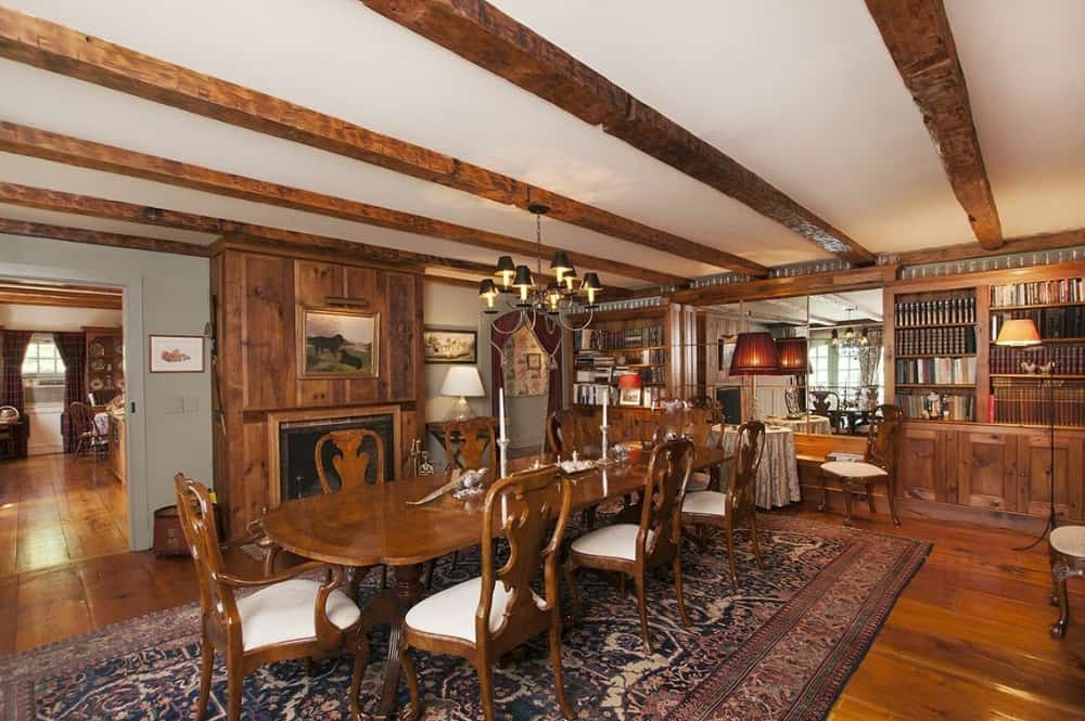 The dining room offers a large oval-shaped dining table paired with classy wooden chairs, set on top of an area rug. There's a fireplace on the side of the room as well. Images courtesy of Toptenrealestatedeals.com.