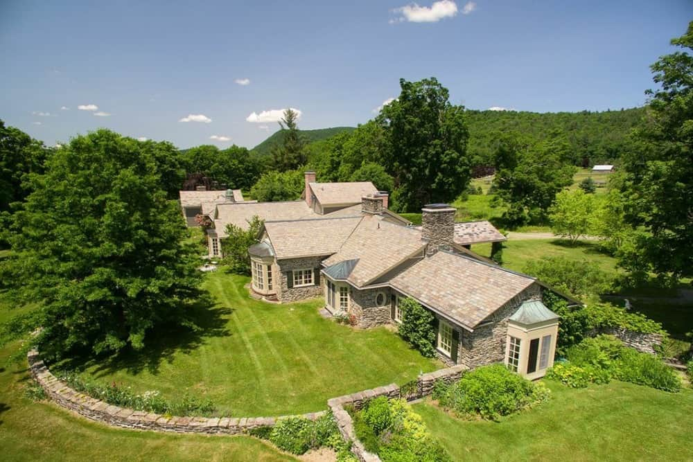 Aerial view of the property showcasing the beautiful architectural design of the house along with its landscaping.