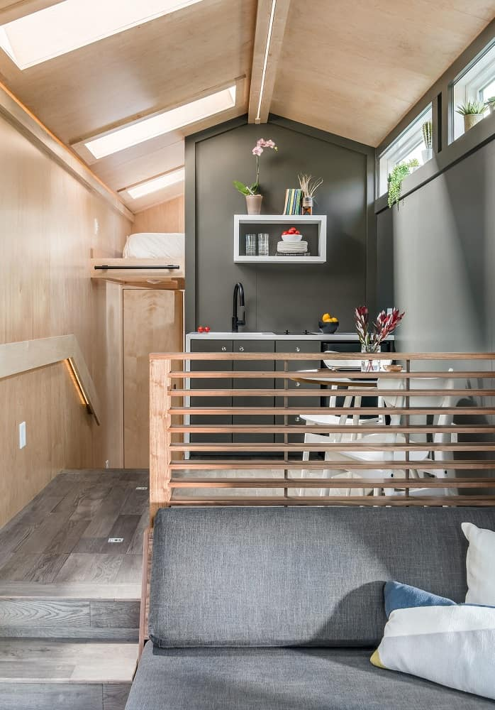 Living area to kitchen in the Orchid Tiny House designed by New Frontier Tiny Homes.