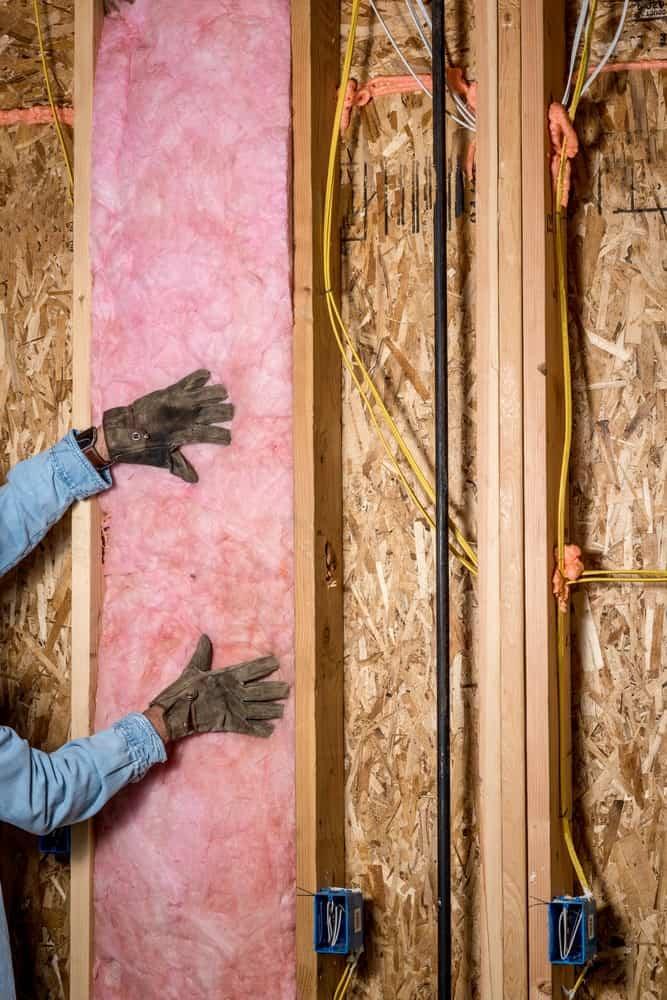 Pink insulation installed between wood studs.