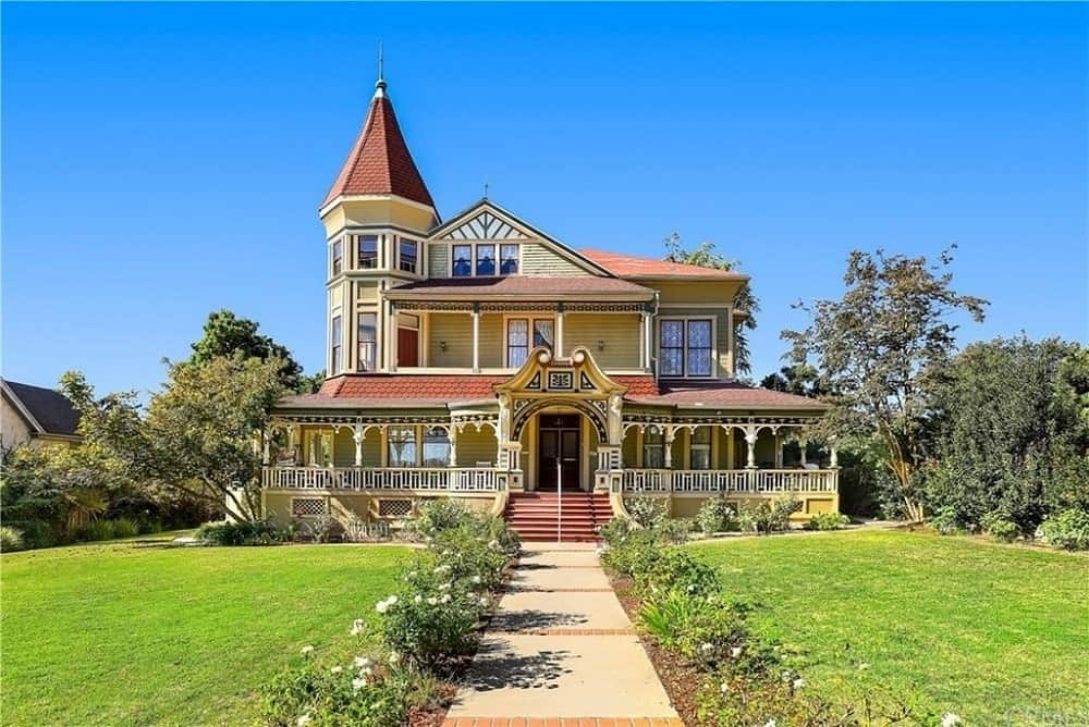 This beautiful home has a welcoming and warm vibe to its terracotta-colored roof and sunny yellow exterior walls. Both levels of the home are designed with its own outdoor area that looks over the beautiful front yard that has a walkway in the middle lined with white flowering shrubs and lawns of grass matching with the tall trees on the sides.