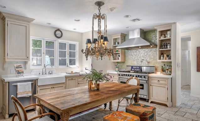 The home also has a dine-in kitchen, featuring an L-shaped kitchen setup with a fancy dining table and chairs set lighted by a glamorous chandelier. Images courtesy of Toptenrealestatedeals.com.