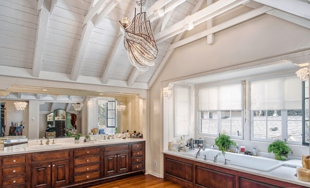This primary bathroom features hardwood floors and a tall vaulted ceiling with exposed beams. The room has a double sink and a drop-in bathtub. Images courtesy of Toptenrealestatedeals.com.
