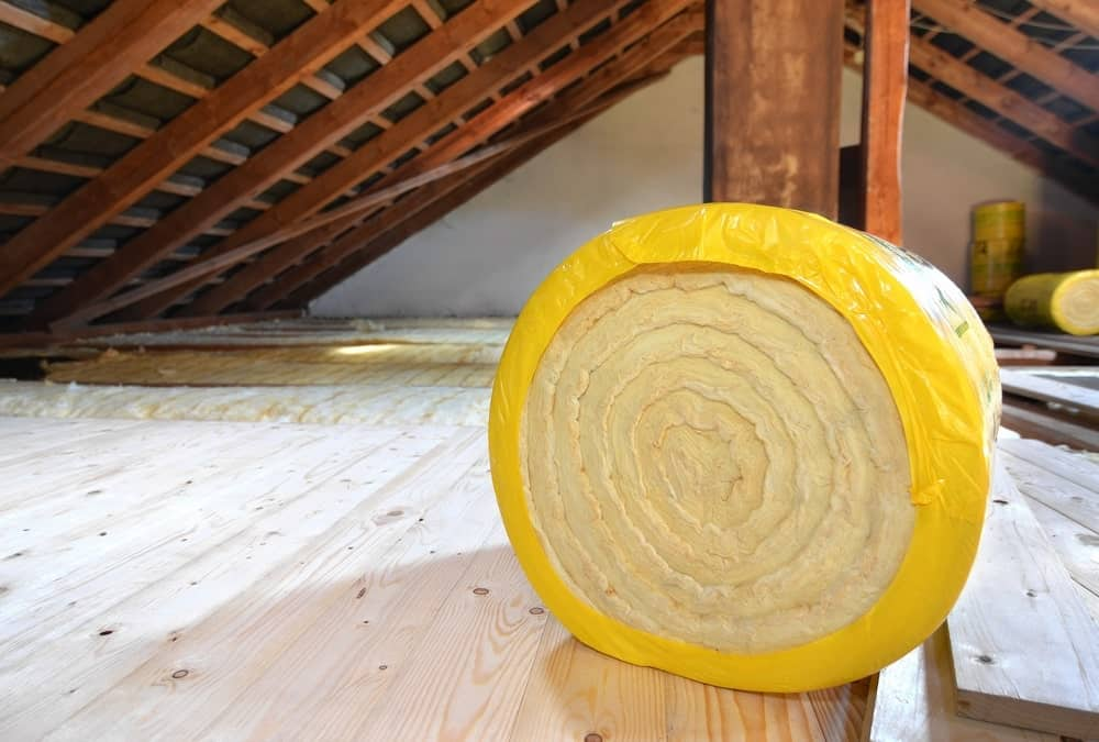 A roll of insulating glass wool on an attic floor.