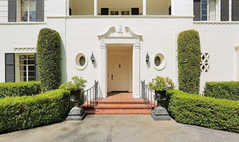 A look at the house's main entry. This entry has a three-steps staircase with iron railings on both sides. Images courtesy of Toptenrealestatedeals.com.