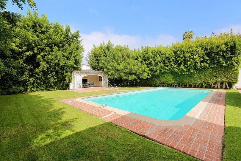 A look at the home's large swimming pool surrounded by the lush lawn and mature trees. Images courtesy of Toptenrealestatedeals.com.