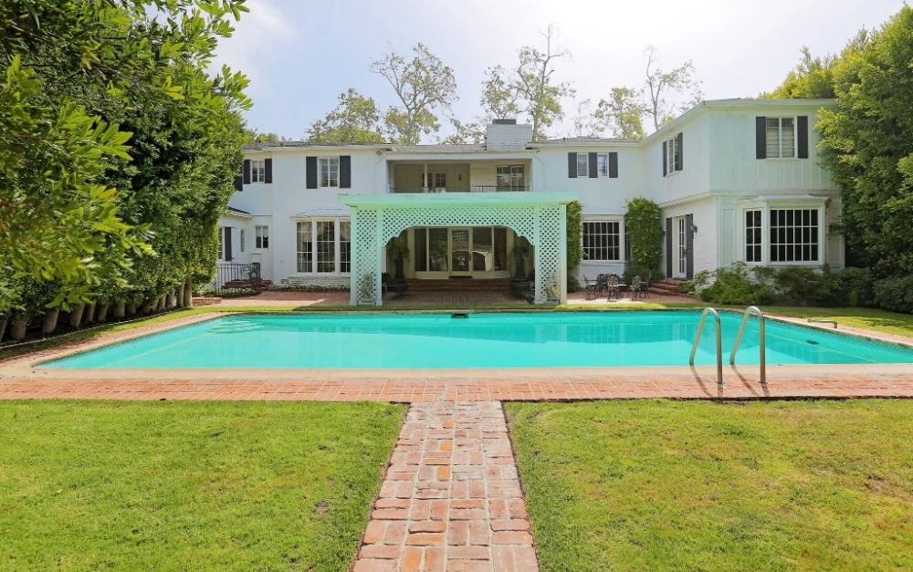An outdoor view of the property showcasing the lush lawns and large swimming pool, along with the house's white exterior.