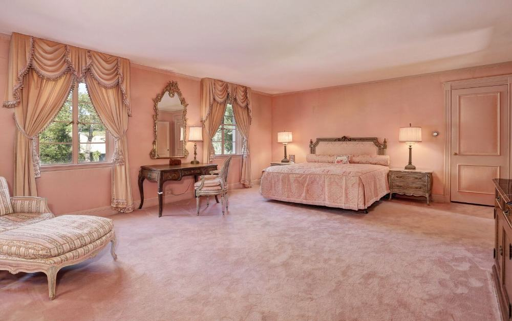 Large primary bedroom featuring pink walls, pink carpet flooring and pink window curtains. The room offers a large comfy bed and a make up desk on the side. Images courtesy of Toptenrealestatedeals.com.