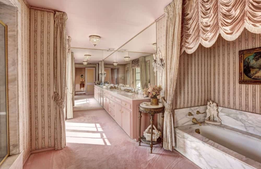 Large primary bathroom boasting classy walls and tiles flooring. It offers a double sink counter and an elegant drop-in soaking tub on the side. Images courtesy of Toptenrealestatedeals.com.