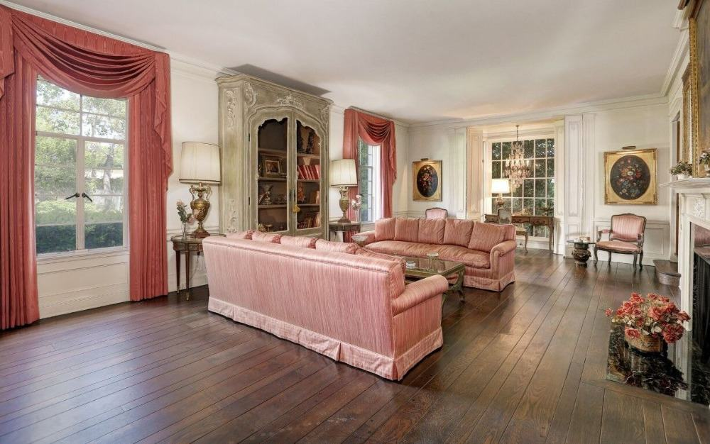The formal living room offers a set of charming couches with a stylish center table. The room features hardwood floors and offers a fireplace. Images courtesy of Toptenrealestatedeals.com.