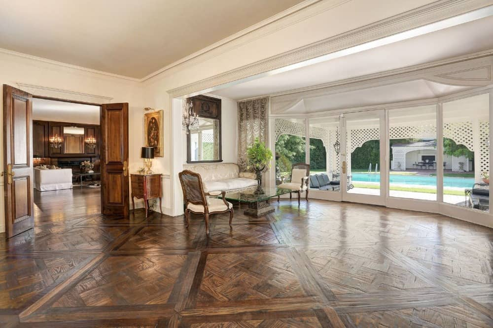 Here's a large hall of the house featuring a sitting area on the side with classy seats. There's a doorway leading straight to the backyard where the swimming pool is set. Images courtesy of Toptenrealestatedeals.com.