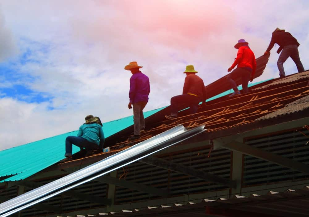 Contractors repairing the house roof.