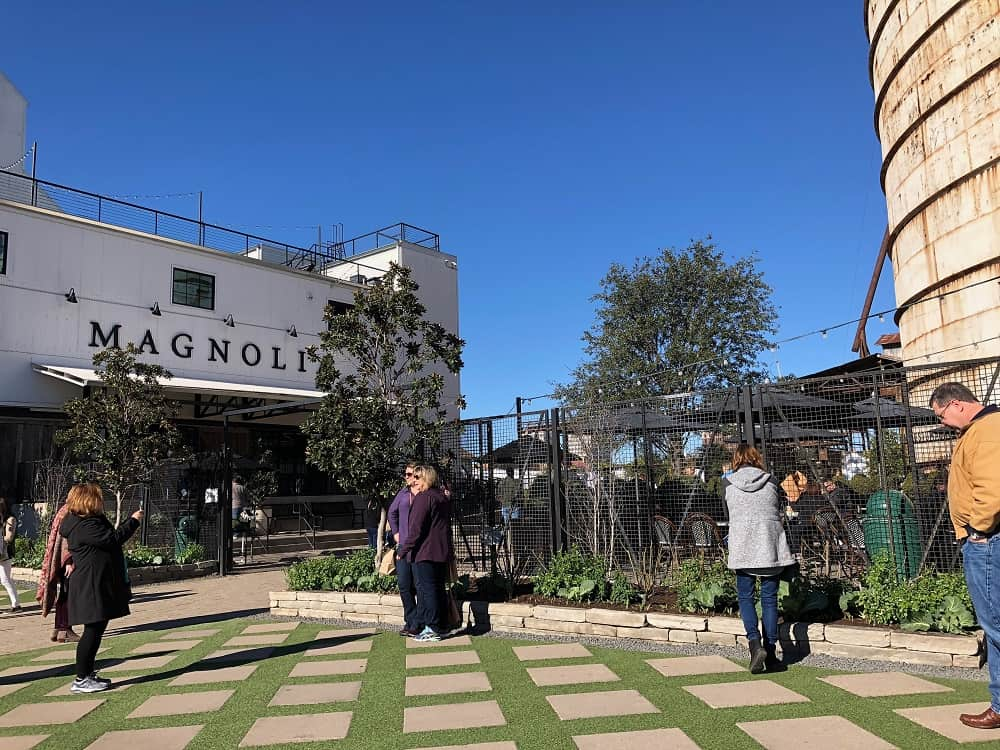 The beautiful pavement of the walkway to Magnolia Market styled with concrete squares alternating with grass.