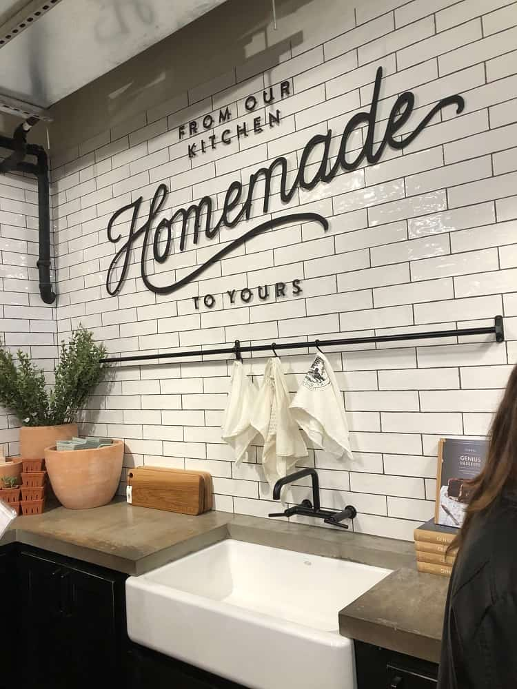 A display of the farmhouse-style kitchen set-up in the kitchen section of the Magnolia Market with white subway tiles.