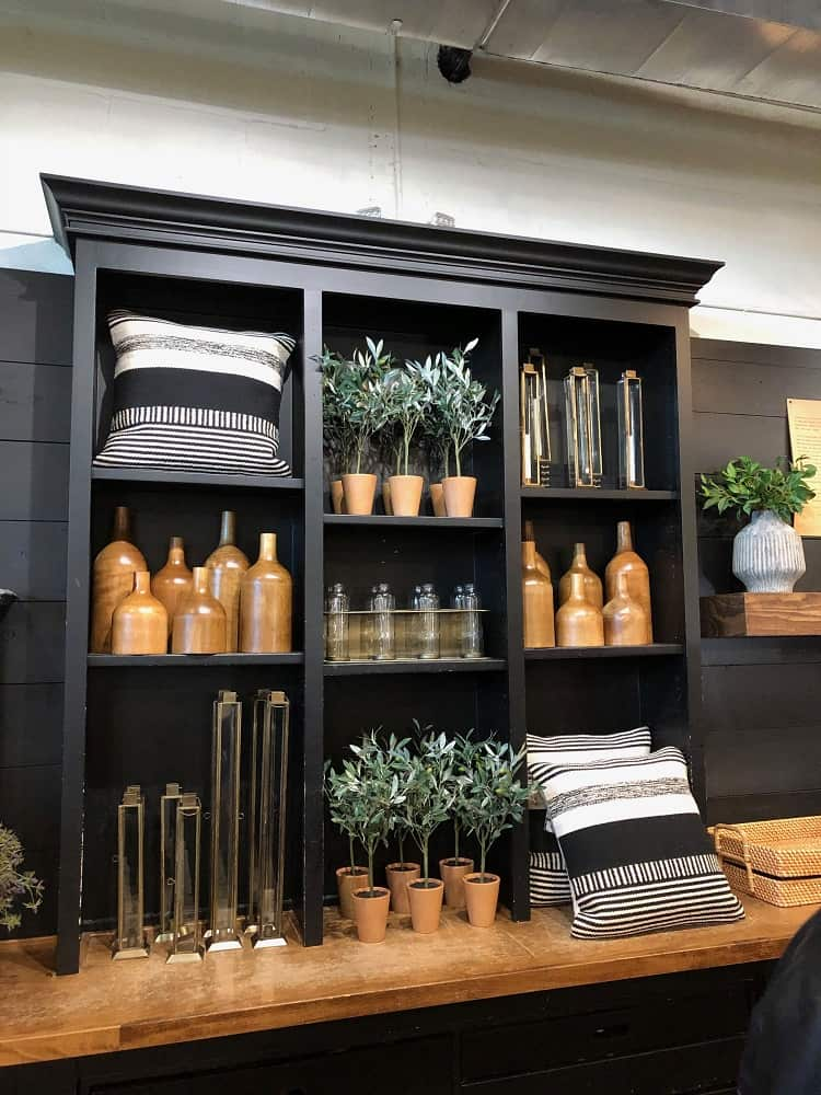 Beautiful Farmhouse-style decors for sale on display with a lovely black wooden shelf.