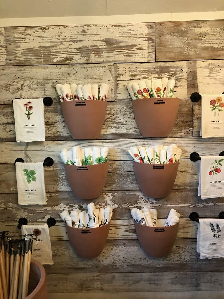 Sets of plant-themed hand towels on display on a distressed shiplap wooden wall.
