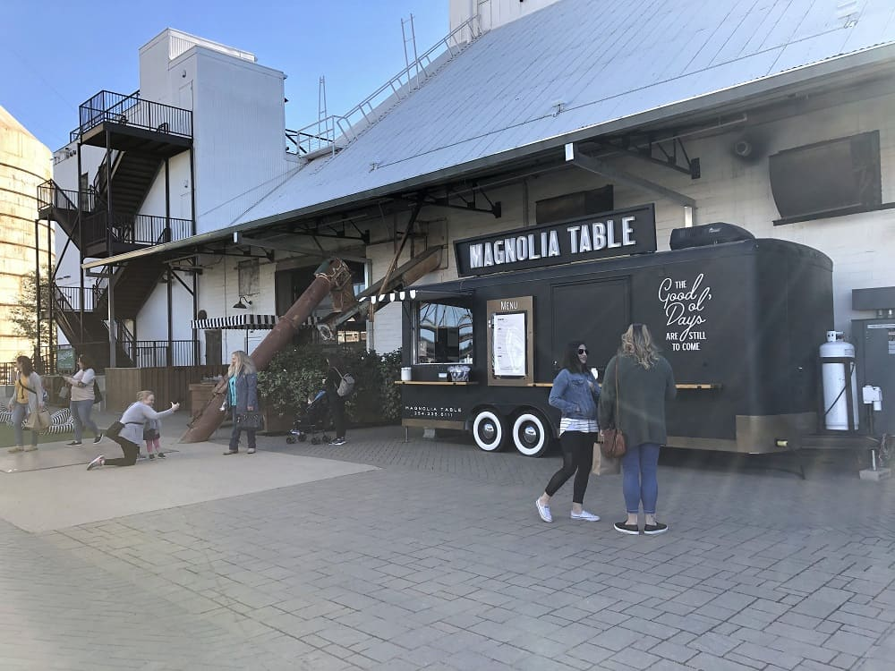 A Magnolia Table Food Truck with a lovely black color to match the concrete walkway.