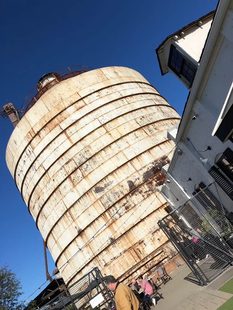 One of the historical silos of Magnolia Market with several outdoor eating areas at the base.