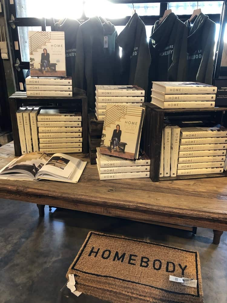 Displayed books, jackets and welcome mats with the distinct Magnolia brand for sale.
