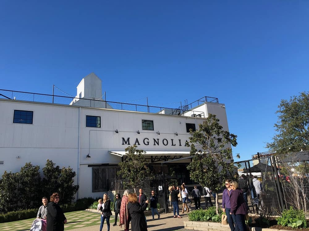 The main entrance of Magnolia Market and Silos viewed from the walkway with several tourists.