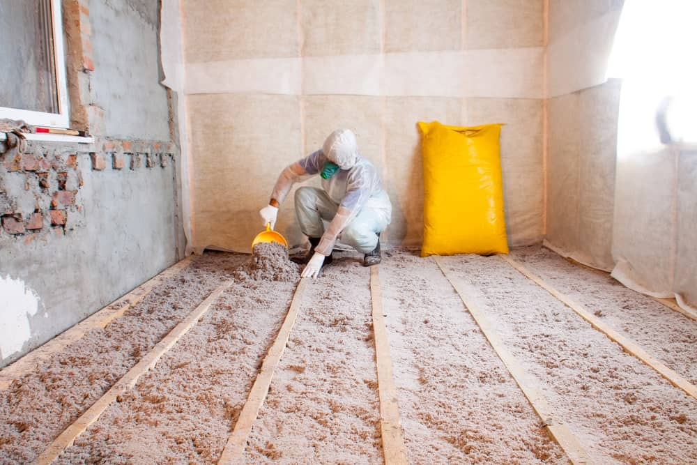Man stacks eco-friendly sheep's wool to the floor of the house for preservation and thermal insulation.