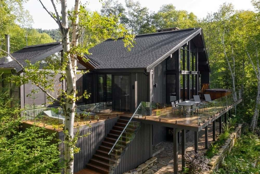 This simple yet charming two-storey cottage home is surrounded by various greenery of tall trees, shrubs and grass that work quite well with the black matte exterior walls of the house. There are shaded areas to dine outside on the second floor balcony as well as an outdoor cooking area.