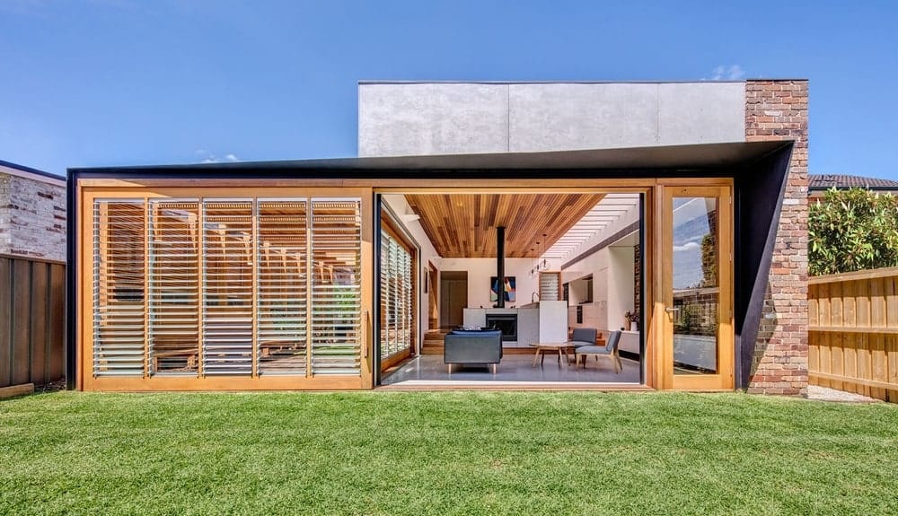 This gorgeous home has a unique design of a large sliding door that enables the living room area to be open to the backyard of green grass lawn. The property is surrounded by charming wooden fences that totally match the wooden panels of the home complemented by the bricked exterior wall on one side.
