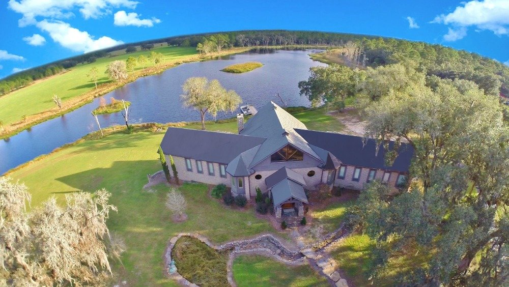 Aerial view of the house showcasing its gorgeous exterior and the lovely natural landscape surrounding it.