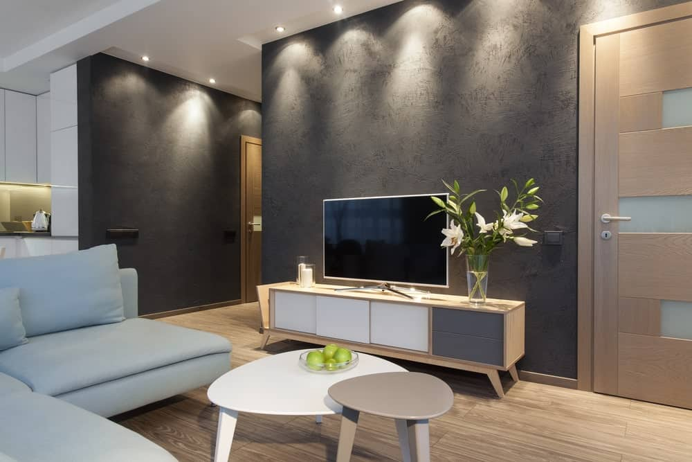 Small living room with wide plank flooring, gray textured walls, recessed lights, L-shaped sofa, modular coffee table and a flatscreen TV over a light wood rack.