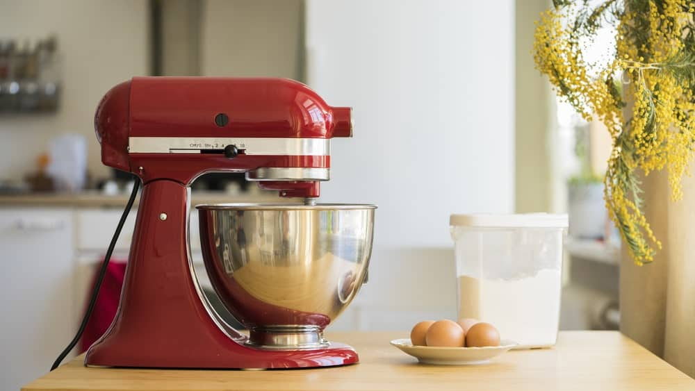 A red stand mixer with cream sits on a desk beside other ingredients.
