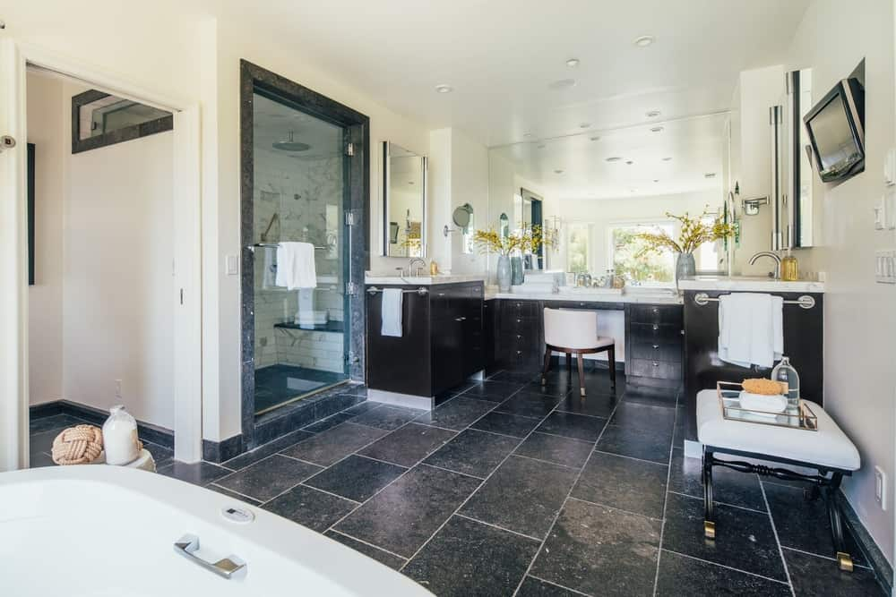 The master bathroom is large, featuring black tiles flooring and is offering a freestanding soaking tub and a walk-in corner shower room. Images courtesy of Toptenrealestatedeals.com.