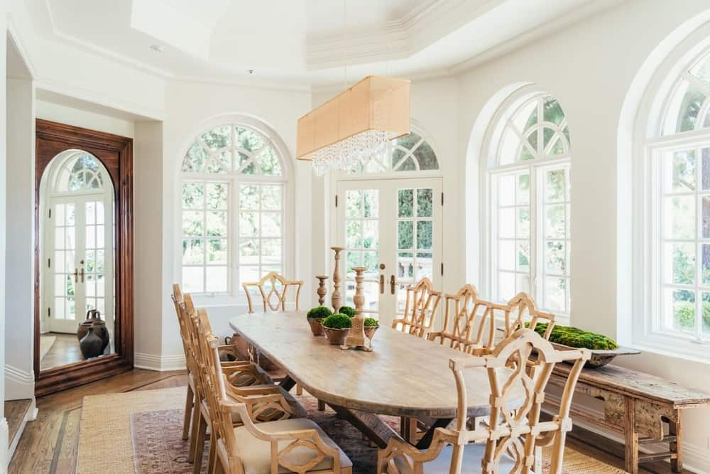 A focused look at the dining room's oval-shaped wooden dining table and chairs set lighted by a gorgeous ceiling light. Images courtesy of Toptenrealestatedeals.com.