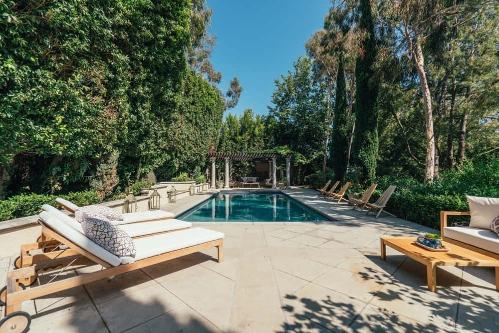 The house also offers a rectangular swimming pool offering multiple sitting lounges on the side, and is surrounded by healthy and mature trees. Images courtesy of Toptenrealestatedeals.com.