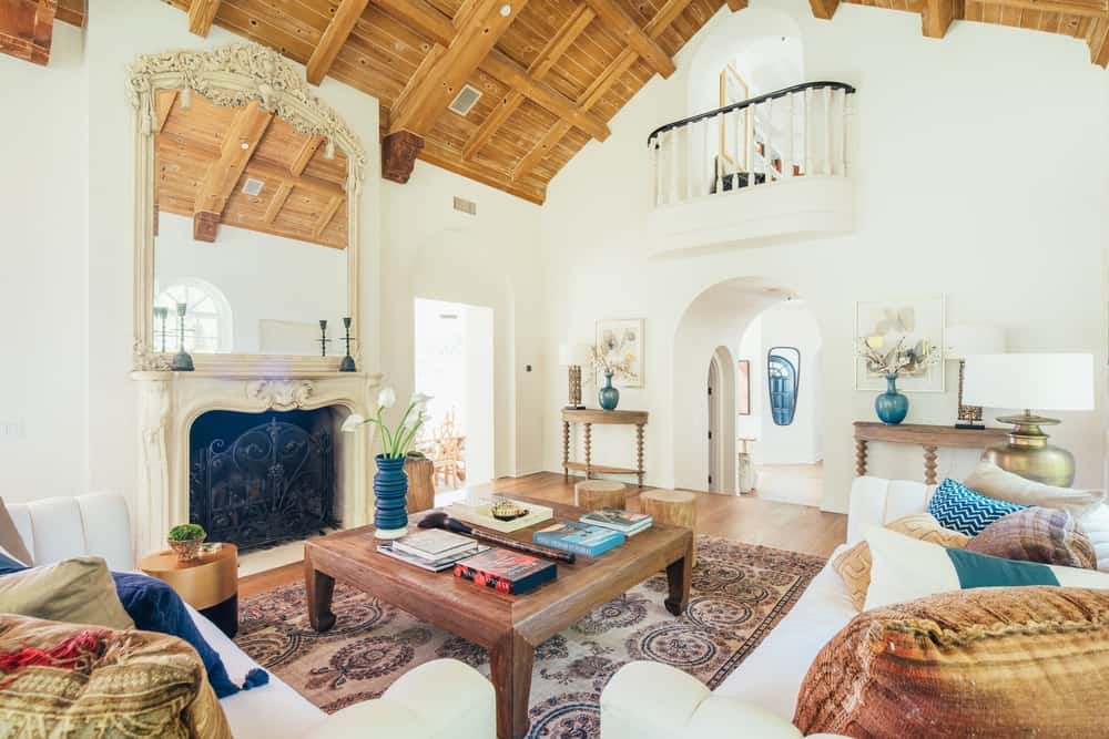 A formal living room with a set of comfy seats and a classy wooden center table, along with an elegantly-designed fireplace set. This living room is set under the home's tall vaulted ceiling with beams.