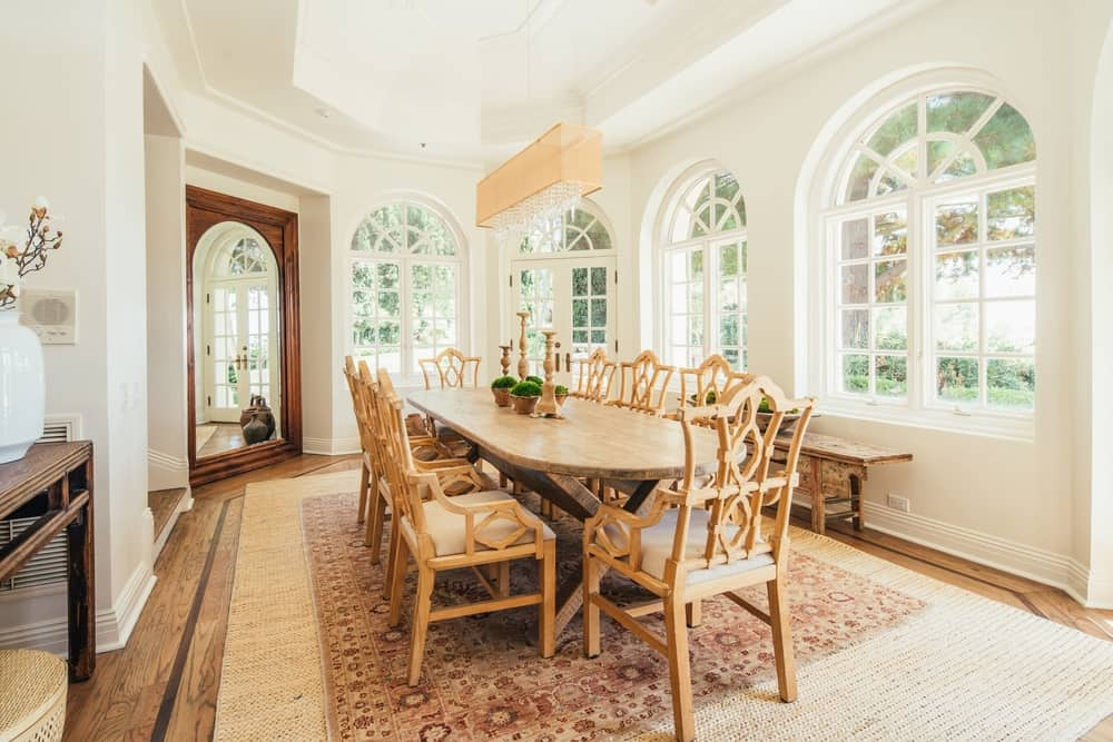 The dining room offers a large oval wooden dining table and chairs set on top of a massive area rug covering the hardwood flooring. Images courtesy of Toptenrealestatedeals.com.