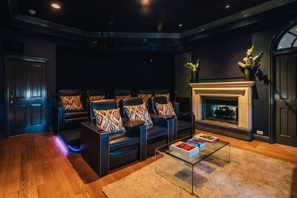 The home theater of the house features sectional seats surrounded by black walls. The room also features vinyl flooring. Images courtesy of Toptenrealestatedeals.com.