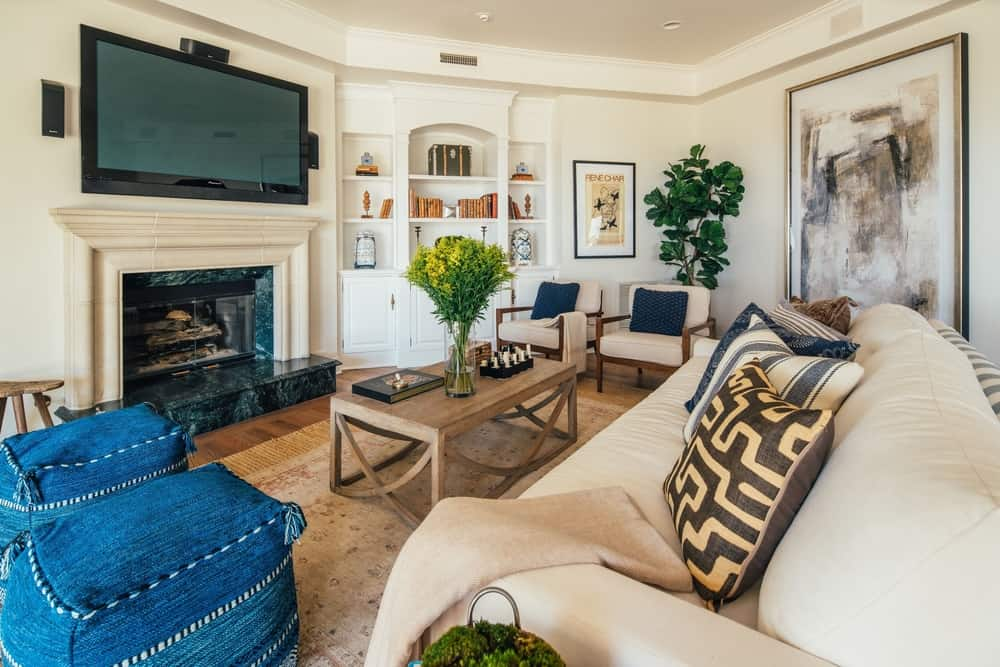 Here's a family room offering a set of comfy seats along with a rustic center table and a fireplace with a large widescreen TV set in front of the sofa. Images courtesy of Toptenrealestatedeals.com.