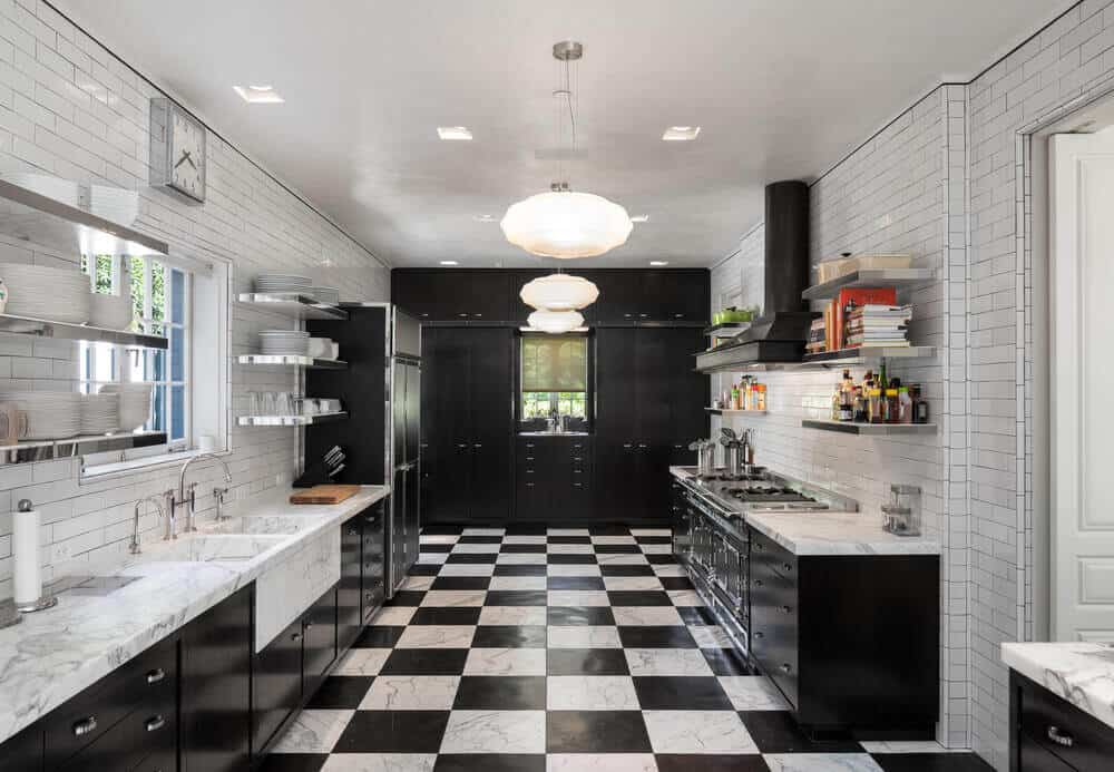 A spacious kitchen featuring tiles walls and checkered tiles flooring. It has three counters, both with marble countertops. The area is lighted by recessed and pendant lights.