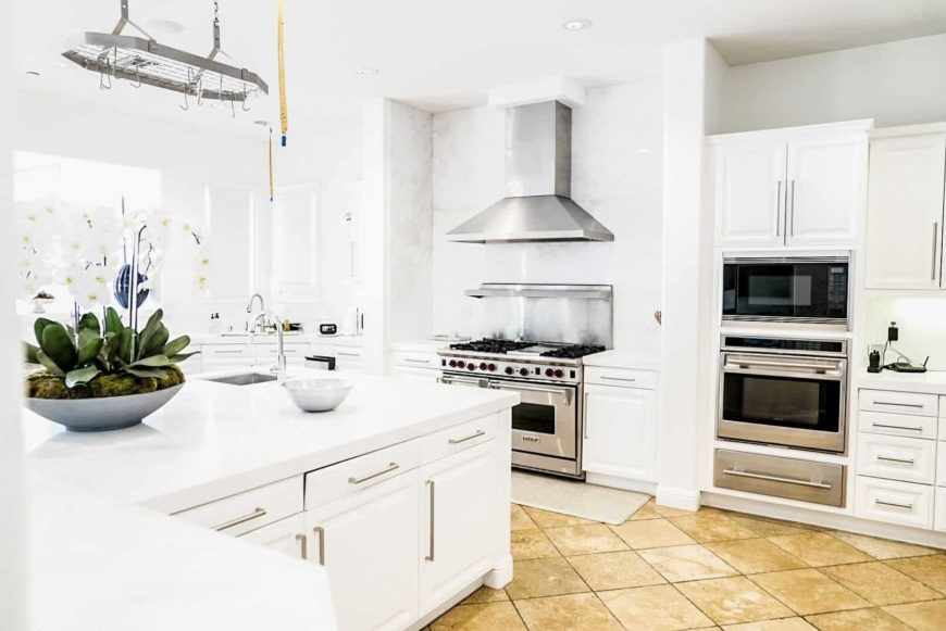 A bright kitchen featuring white walls and a white ceiling with beige tiles flooring. The kitchen offers white kitchen counters with white countertops.