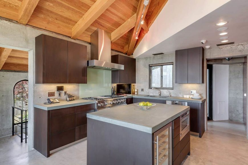 L-shaped kitchen with a gray countertop and brown cabinetry. There's also a center island.