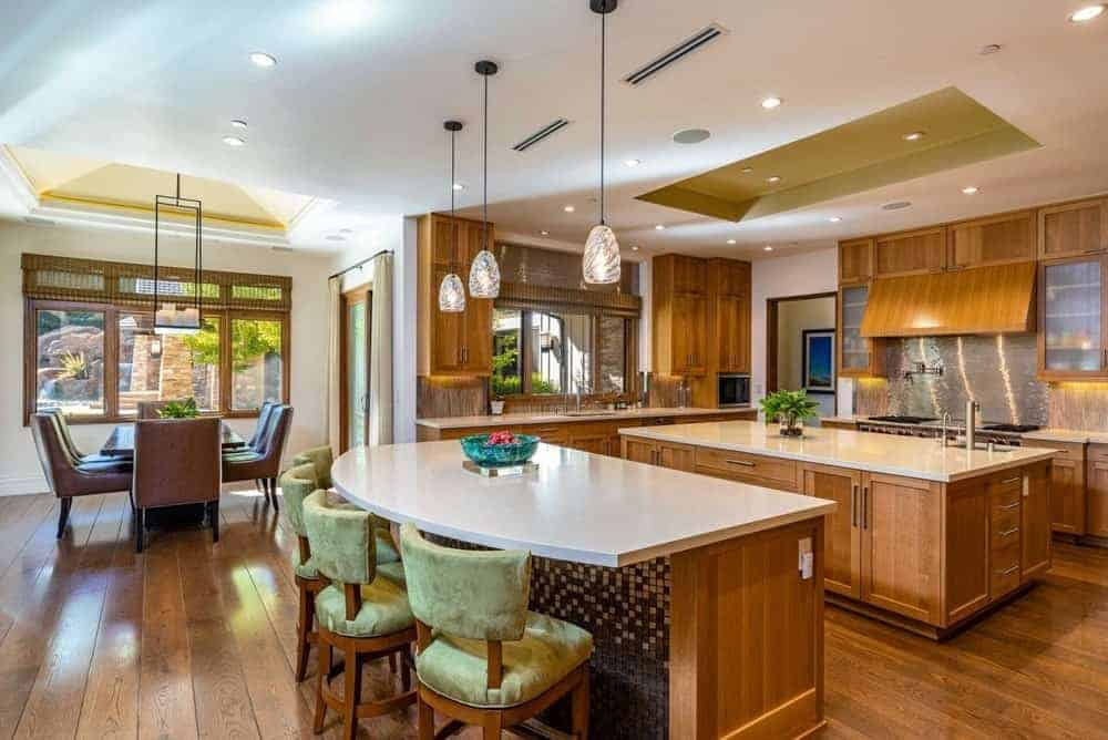 Large dine-in kitchen hardwood floors and a custom ceiling. It has a center island and a breakfast bar island lighted by recessed and pendant lights.