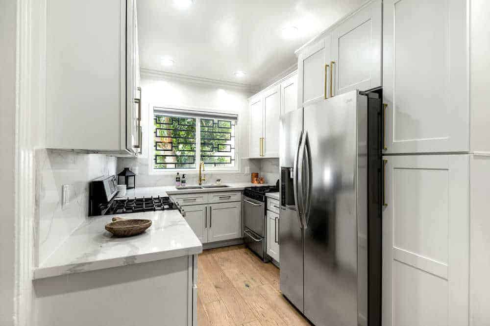 A small kitchen area featuring a marble kitchen countertop and hardwood flooring, along with a ceiling with recessed ceiling lights.