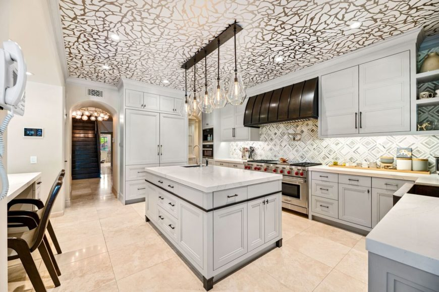 Large kitchen boasting a stunning ceiling design and beige tiles flooring. It offers an L-shaped kitchen counter along with a center island lighted by pendant lights.