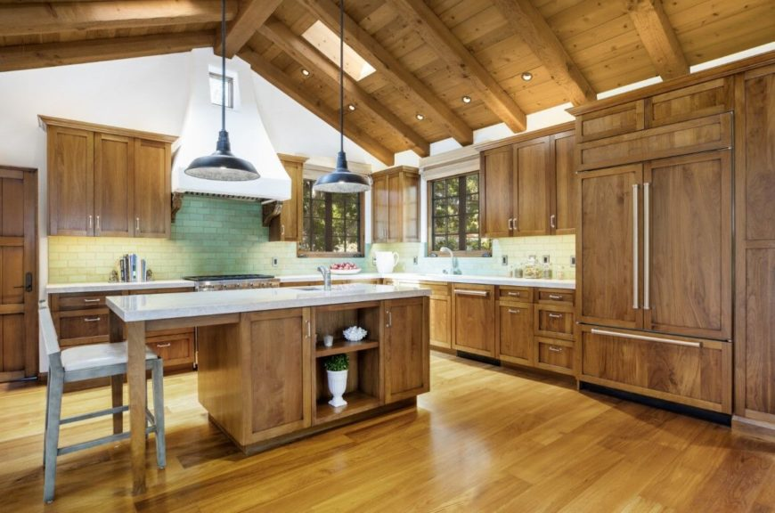 L-shaped kitchen featuring hardwood floors, a tall vaulted wooden ceiling with beams and brown cabinetry and kitchen counter. There's a center island lighted by pendant lights.
