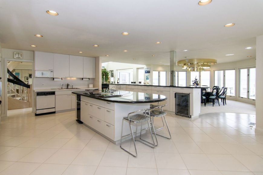 A spacious kitchen featuring tiles flooring and a regular ceiling with scattered recessed ceiling lights. There's a center island with a black countertop along with space for a breakfast bar.