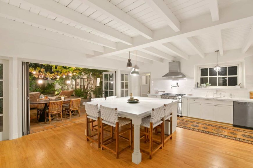 A spacious dine-in kitchen featuring white walls with beams and hardwood floors. The area offers a white center island with a breakfast bar for six.